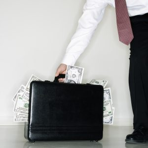businessman carrying briefcase overflowing with money.
